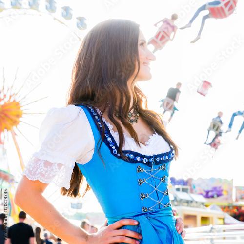 Fototapeta Frau im Dirndl steht lächelnd vor Riesenrad und dem Kettenkarussell auf bayrischem Volksfest obraz na płótnie