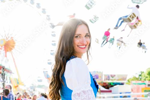 Plakát  Frau im Dirndl steht lächelnd vor Riesenrad und dem Kettenkarussell auf bayrisch