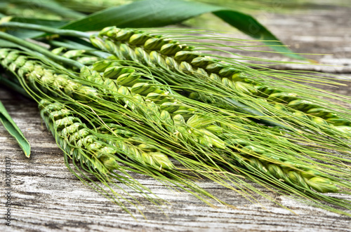 Green ears of wheat on wooden background. Grain harvest on the table.
