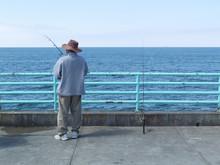 Man Fishing At Pier Of Manhattan Beach, Los Angeles, CA