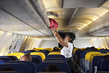 Traveller Woman Open Overhead Locker On Airplane