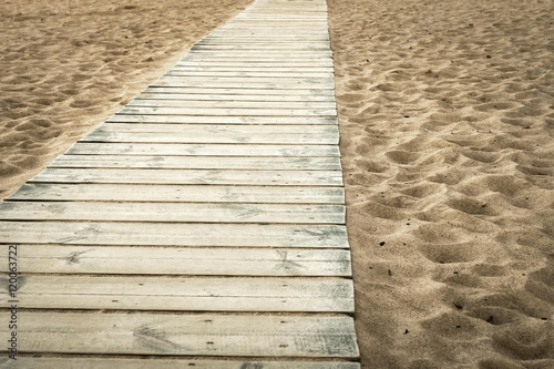 wooden scaffold on the sandy beach of color sepia Poster