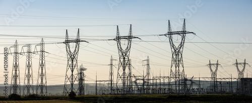 Valokuva  Electricity transmission pylon silhouetted against sunset sky