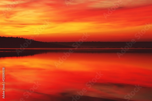Poster de jardin Rouge beautiful sunset red and orange above the water surface of the lake. hilly shore away with silhouettes of trees. anyone.