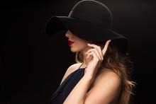 Beautiful Woman In Black Hat Over Dark Background