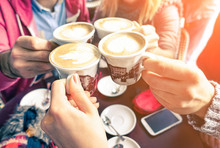 Group Of Friends Cheers With Cappuccino Cup In Cafe Bar With Phone On Table - Family Having Fun Drinking Together At Restauran In Winter Season Closeup Scene With Soft Vintage Filter And Sun Halo