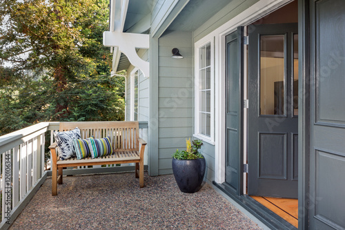 Fotomural  Entrance porch decorated with antique bench, big flower pot with