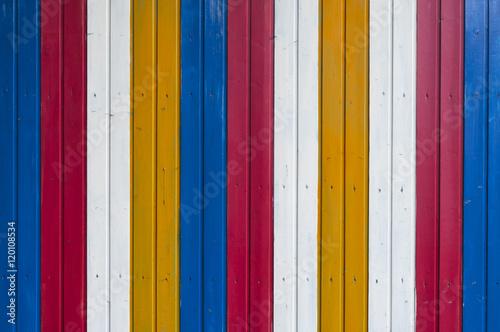 Fotografie, Obraz  Bunter Holz Hintergrund / Hintergrund aus einer bunten Holzwand gestreift weiss, gelb, blau, rot