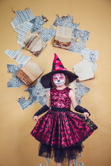 Girl in witch costume and makeup on her face standing  the background of yellow wall