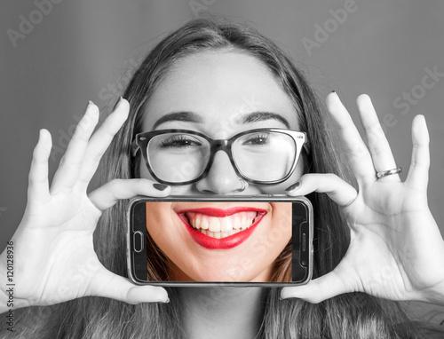 ragazza con smartphone che si scatta una foto al proprio sorriso Wallpaper Mural