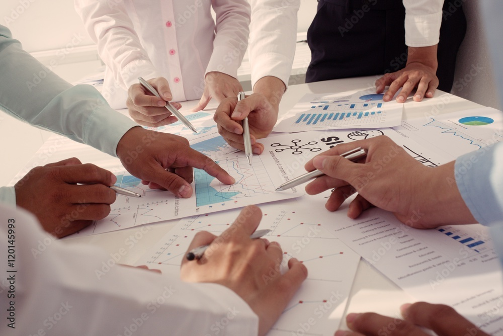Fototapeta Group of business peopleworking with papers together