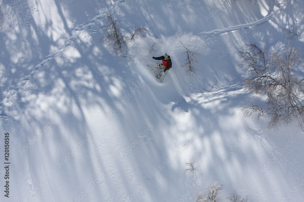 Fotografie, Obraz  Snowboarder Carves a Slash While He Rides Down the Snowy Mountain Terrain at the