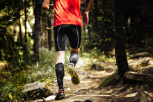 Marathon Runner Running On Stones In Forest, On Feet Compression Socks. Closeup Of Trainers