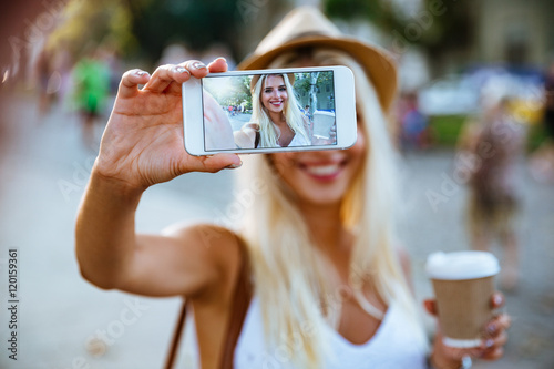 Cuadros en Lienzo Young smiling girl making selfie while standing on the street
