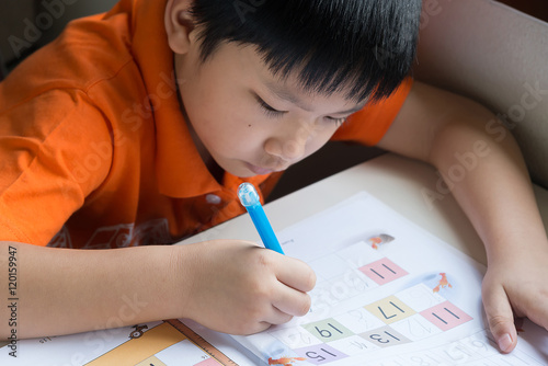 Photo  Little Boy Writing Math Exercise At Home.