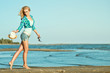 Young beautiful slim blond girl is running along the seaside with hat and sunglasses in her hands. She is smiling and looking back. Sea resort and summer fashion concept. Outdoor shot. Copy-space