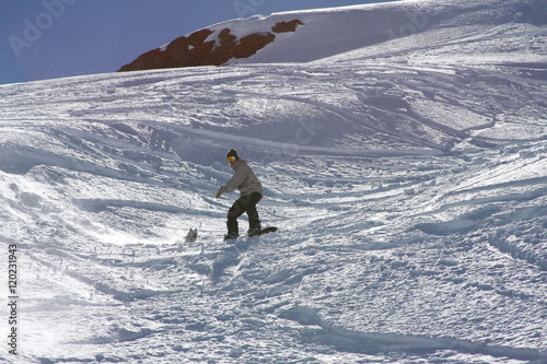 Obraz na plátně  Man Snowboarding With His Dog on an Adventure in the Snow Covered Mountains