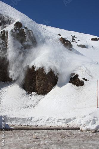 Fotografie, Obraz  Snowboarder Does a Big Air Jump Near Some Steep Rock Cliffs