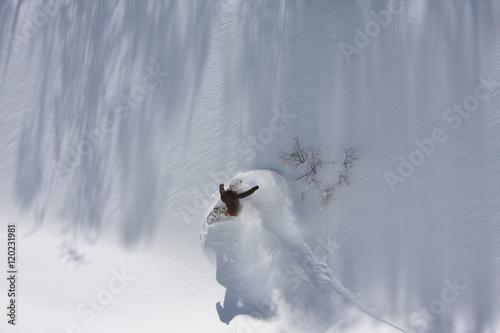 Fotografie, Obraz  Snowboarder Carving a Powder Turn in a Wall of Fresh Powder Snow