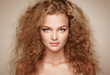 Leinwandbild Motiv Fashion portrait of young beautiful woman with jewelry and elegant hairstyle. Redhead girl with long curly hair. Perfect make-up