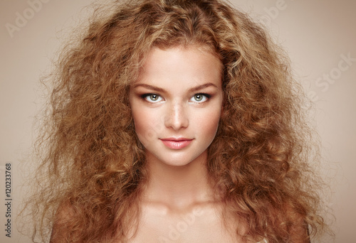 Fashion portrait of young beautiful woman with jewelry and elegant hairstyle. Redhead girl with long curly hair. Perfect make-up