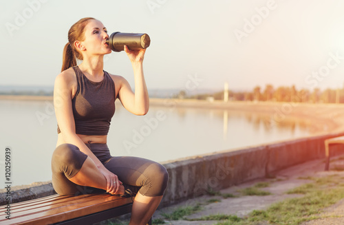 Fotografia  Young girl with a shaker water outdoors