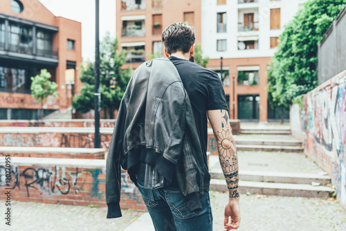 From behind knee figure view of young beautiful caucasian bearded tattooed man strolling through the street of a city olding leather jacket