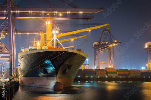 Tela Container Cargo freight ship with working crane bridge in shipyard at dusk for Logistic Import Export background