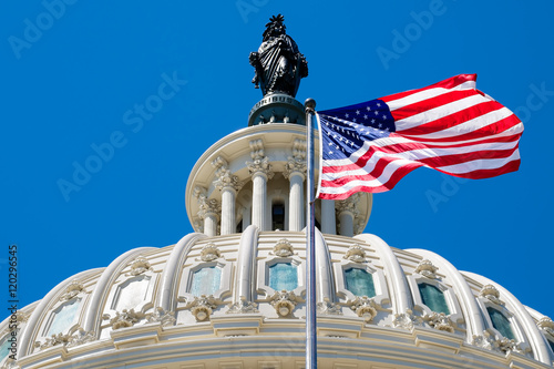 Photo The american flag waving in front of the Capitol dome in Washing