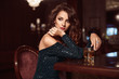 canvas print picture - Beauty young brunette woman sitting at the bar