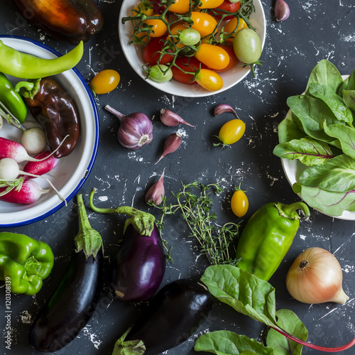 Foto  Fresh vegetables - radishes, eggplant, pepper, tomatoes, onion, garlic on a dark wooden background