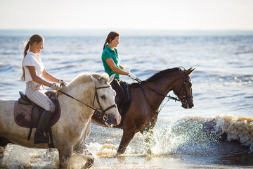 Two pretty girls riding horses in river water
