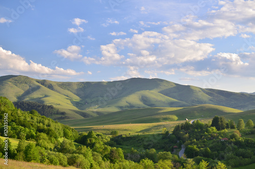 Foto auf Gartenposter Hugel Landscape of Zlatibor Mountain. Green meadows and hills under blue sky with some clouds in springtime