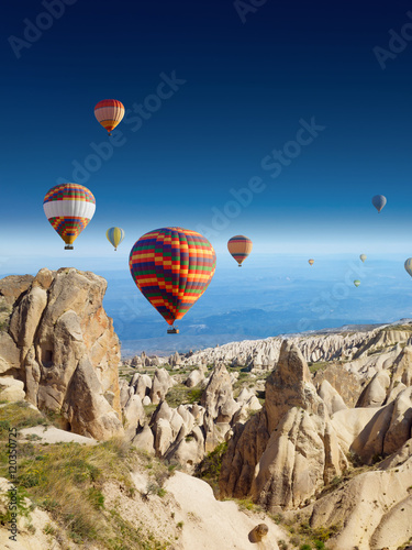 Poster Montgolfière / Dirigeable Hot air balloons flies in clear deep blue sky in Cappadocia