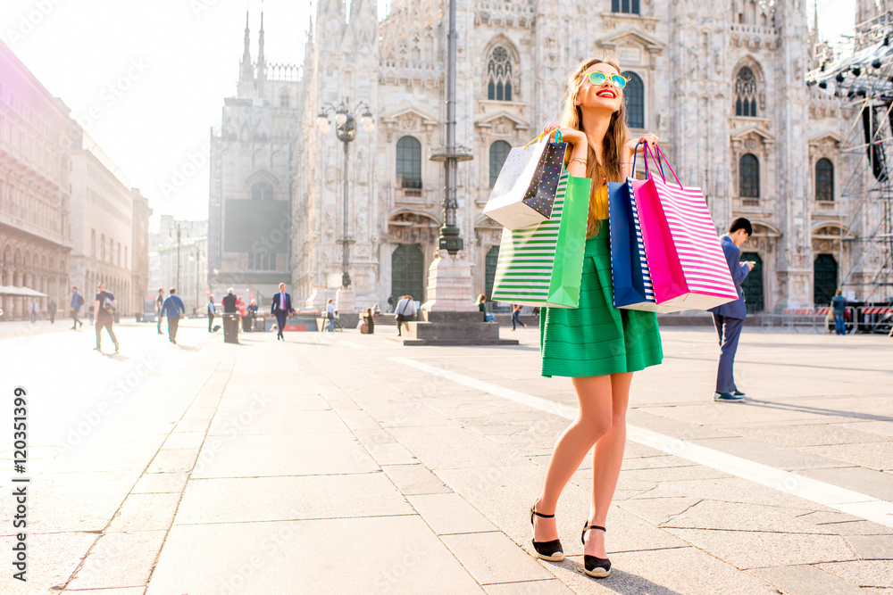 Fototapeta Young woman standing with colorful shopping bags on the main square in front of the famous duomo cathedral in Milan. Happy shopping weekend in Milan
