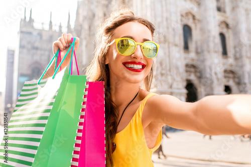 Plakat Młoda kobieta robi selfie portretowi z kolorowymi torba na zakupy na głównym placu przed sławną duomo katedrą w Mediolan. Szczęśliwy weekend na zakupy w Mediolanie