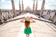 Back View On The Female Traveler Standing On The Rooftop Of Duomo Cathedral In Milan. Having Great Vacations In Milan