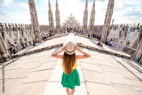 Fototapeta Back view on the female traveler standing on the rooftop of Duomo cathedral in Milan. Having great vacations in Milan obraz