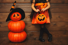 Legs Of Child Girl In Witch Costume  For Halloween With Pumpkin