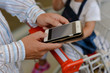 Closeup on father holding mobile phone and daughter in shopping cart, supermarket background. Mock up display smart device