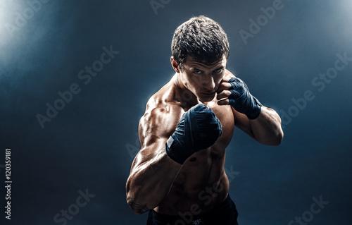 Cuadros en Lienzo Muscular kickbox or muay thai fighter punching in smoke.