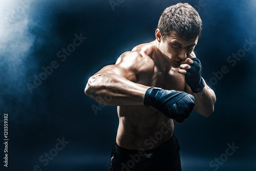 Muscular kickbox or muay thai fighter punching in smoke. Tableau sur Toile