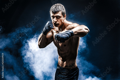 Muscular kick-box or muay thai fighter punching in smoke. Wallpaper Mural