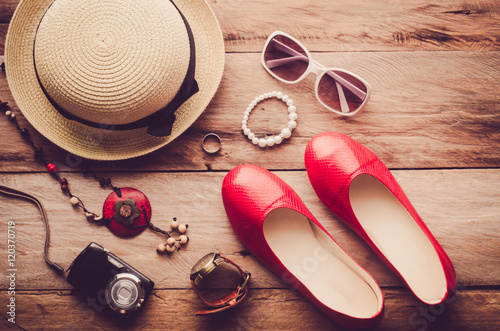 Hats, shoes and accessories to dress lay on the wooden floor for travel - Vintage tone.