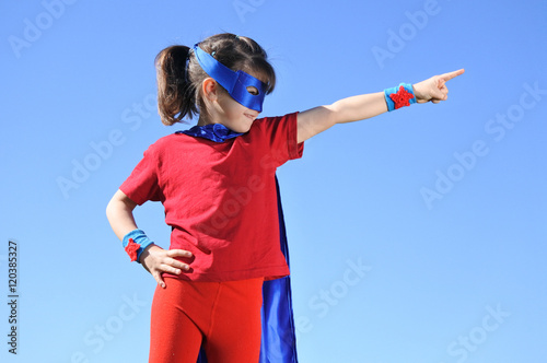 Photo  Superhero girl points towards dramatic blue sky