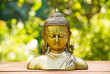 Buddha statue on natural blur green background. Spa concept. Calmness and tranquility. Copy space.