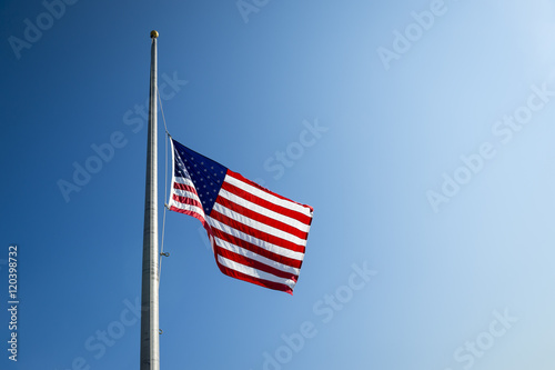 Slika na platnu American flag flies at half mast backlit by the sun in bright blue sky