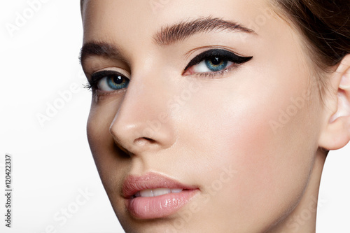 Fényképezés  Girl with clean skin and natural make-up with black arrows on the eyes looking a