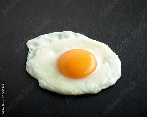 Deurstickers Gebakken Eieren fried egg on black background