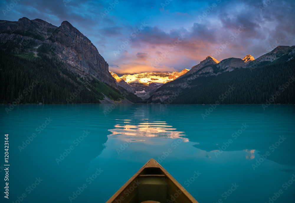 Fototapeta Viewing snowy mountain in rising sun from a canoe